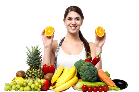 Girl holding sliced oranges with fruits and vegetables around her photo