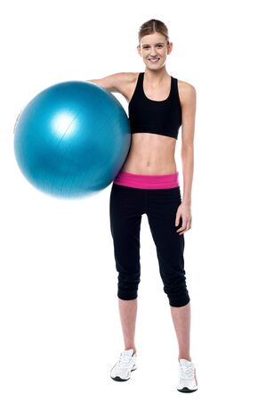 Charming fitness trainer holding pilates ball photo
