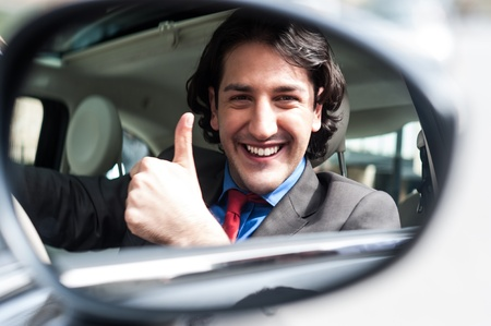 thumps up: Businessman showing thumps up in rear view mirror. Stock Photo