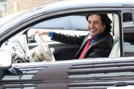 Young professional driving his new luxury car  photo
