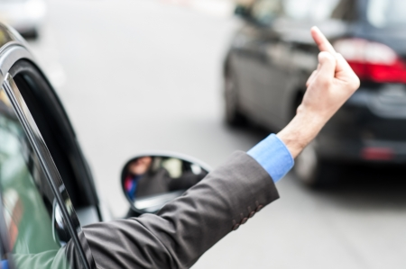 aggressor: Man showing middle finger from car window  Evil gesture  Stock Photo