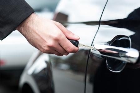 car lock: Man unlocking the door of his car, cropped image Stock Photo