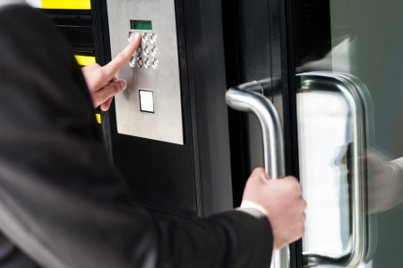security lock: Businessman entering safe code to unlock the door