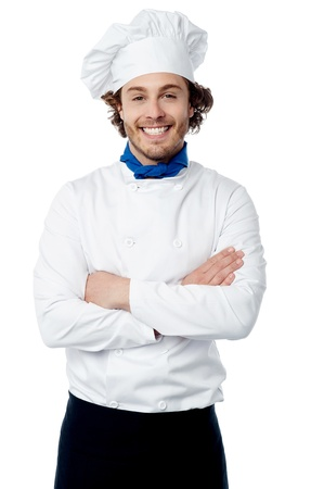 Cheerful young cook posing confidently over white photo