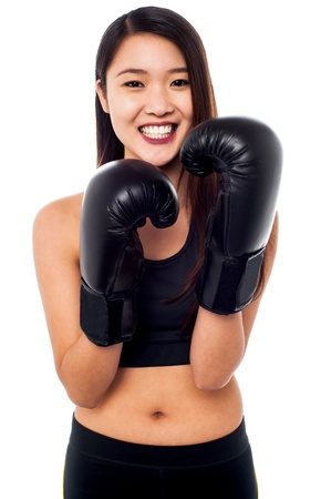 woman boxing gloves: Smiling young girl wearing lightweight boxing gloves