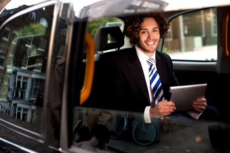 Handsome young businessman on tour, carrying touch pad photo
