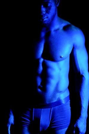 Musculaire jeune homme africain posant sur fond noir