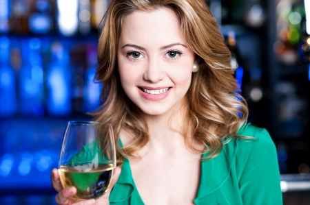 Pretty young girl having wine at a bar photo
