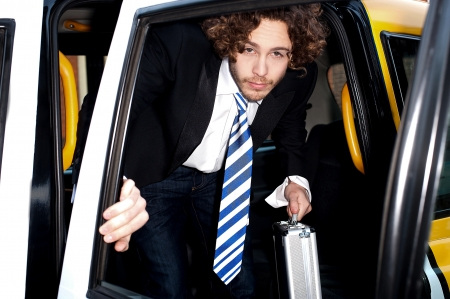 Male passenger stepping out of a taxi cab photo