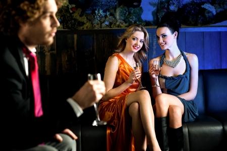 coquetear: Hermosas chicas encantadoras mirando chico joven guapo en un bar