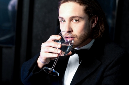 Handsome young guy drinking wine at business party photo