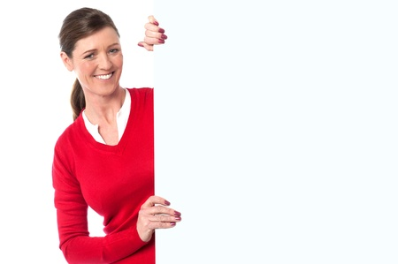 Charming lady holding a blank white ad board photo