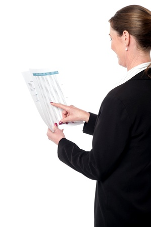 Smiling business lady reviewing annual reports photo