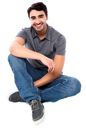 crossed legs: Smart smiling guy sitting on the floor, isolated over white