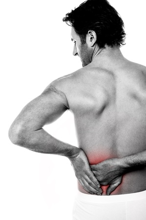 back strain: Young man holding his back, having pain  Stock Photo