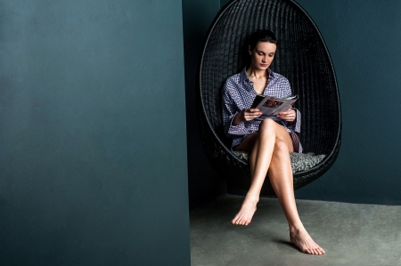 Beautiful woman reading magazine. Sitting on swinging chair with legs crossed photo