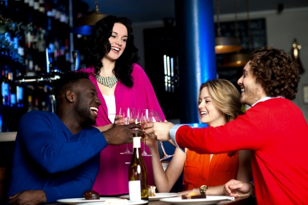 Two young couples in club or bar having fun, toasting wine glasses