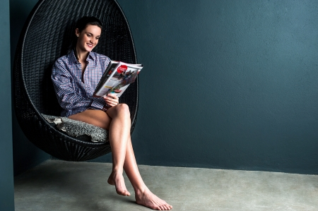 Glamorous woman sitting on bubble chair with legs crossed reading magazine photo