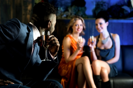 Handsome male staring at attractive young girls in night club Stock Photo