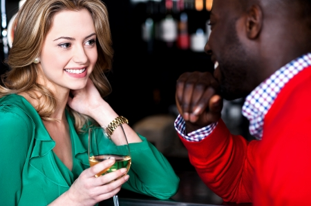 Young couple enjoying at bar, busy in romantic conversation photo
