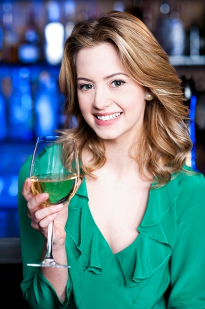 Pretty young girl enjoying sparkling wine photo