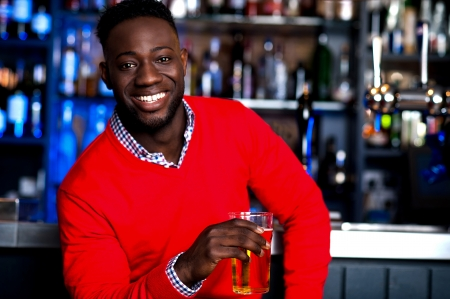 Smiling young african guy enjoying fresh beer at pub photo