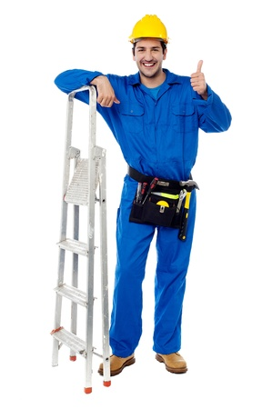 yup: Young construction worker posing with step ladder Stock Photo