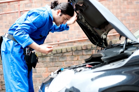 Young car mechanic checking the motor oil photo