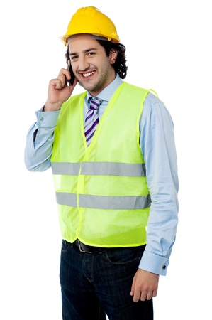 Smart young construction engineer attending call photo