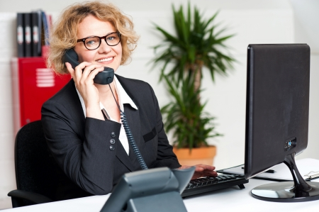 フロント デスクの女性コールに出席し、コンピューターに取り組んで 写真素材