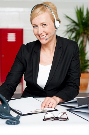 Female executive talking to client through headphones photo