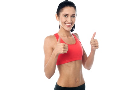 posing  agree: Female gym trainer showing double thumbs up