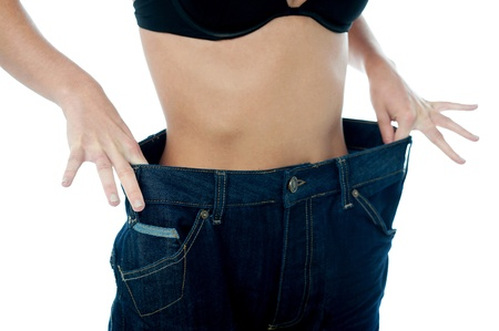 over sized: Woman holding the over sized jeans around waistline