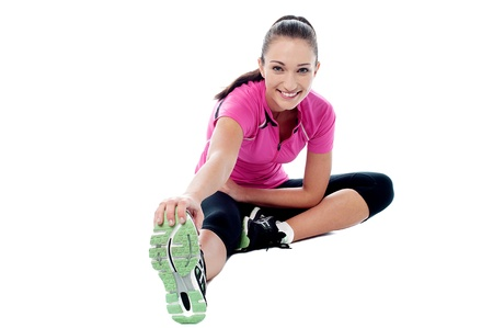 Beautiful young fit woman doing stretching exercise photo