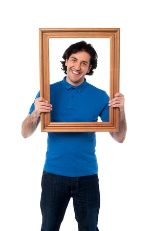 Happy guy looking through empty picture frame photo