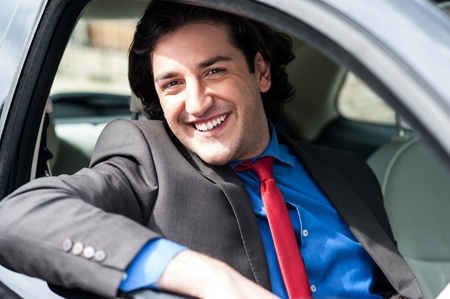 Young businessman driving his new luxurious car photo