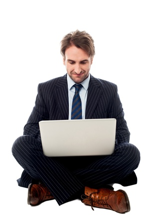 Businessman sitting on floor, working on a laptop photo
