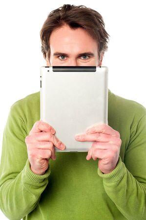 Young guy hiding his face with e-book reader