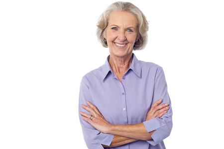señora mayor: Aislada mujer de mediana edad posando con los brazos cruzados Foto de archivo