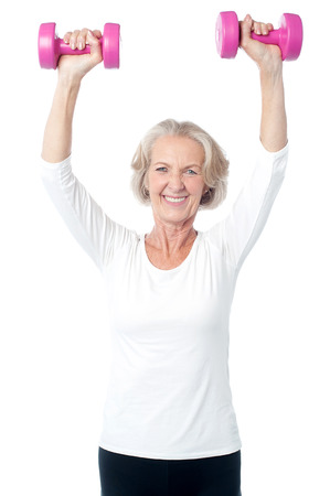Senior lady exercising happily with dumbbells