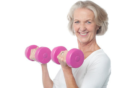 senior citizen: Senior woman in gym working out with dumbbells