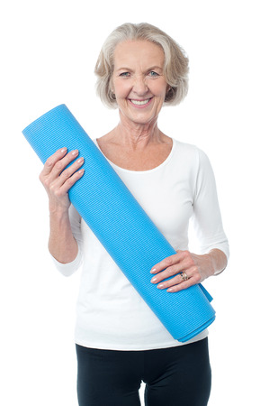 Cheerful female fitness instructor holding blue mat photo