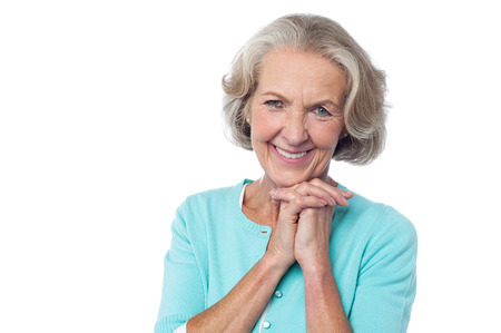 Attractive aged lady posing with clasped hands Stock Photo