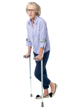 Senior woman walking in pain with help of crutches photo