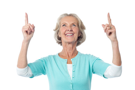upwards: Cheerful old lady seeing and pointing upwards