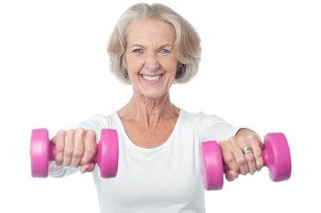 mature female: Senior citizen doing exercise with dumbbells