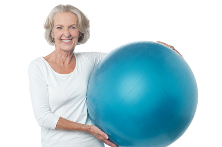 Fit aged woman holding big blue exercise ball photo