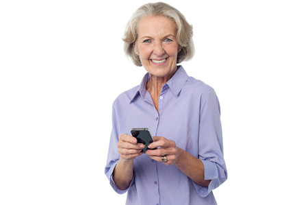 Senior woman messaging to her friend photo