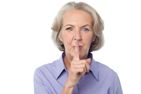 shush: Senior woman gesturing silence