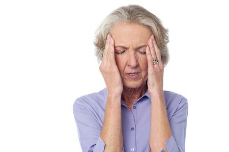 persona confundida: Mujer de edad sosteniendo la cabeza debido al fuerte dolor de cabeza